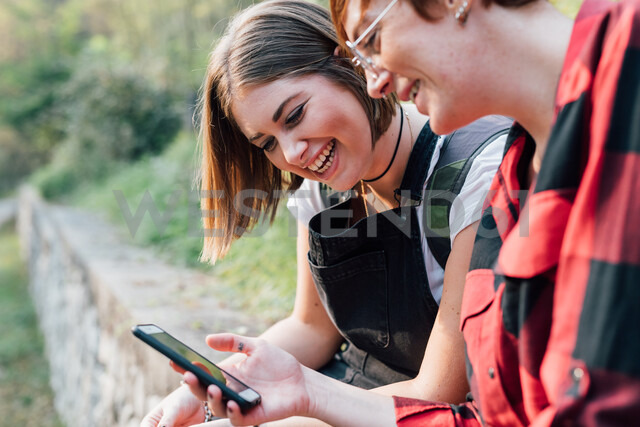 Best friends sitting on stone wall, sharing text message, Rezzago, Lombardy, Italy - CUF50096 - Eugenio Marongiu/Westend61
