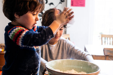 Boys playing with flour in mixing bowl - CUF50117