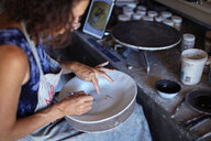 Female potter painting ceramic plate in workshop - CUF50129