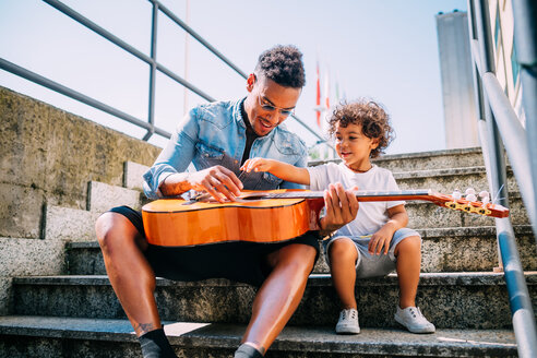 Father teaching son play guitar on stairway - CUF50135