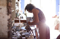 Female potter shaping clay on pottery wheel in workshop - CUF50144
