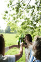 Happy women clinking beer bottles in park - IGGF00988