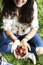 Top view of woman showing berries at a picnic in park - IGGF00994