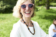 Portrait of happy senior woman wearing sunglasses in park - IGGF00997