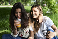 Portrait of two happy young women drinking juice at a picnic in park - IGGF01000
