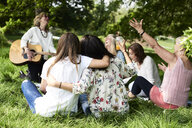 Group of women with guitar having fun at a picnic in park - IGGF01003