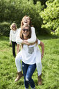 Happy young woman carrying mother piggyback in park - IGGF01012