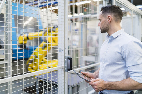 Businessman using tablet in a modern factory - DIGF06655