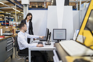 Businessman and businesswoman talking at computer in modern factory - DIGF06700