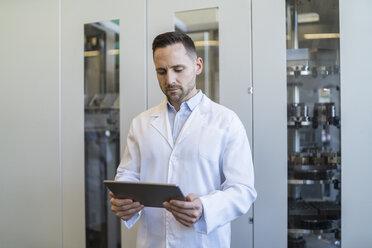 Man using tablet wearing lab coat in modern factory - DIGF06706