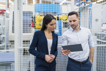 Businessman and businesswoman using tablet in modern factory - DIGF06721