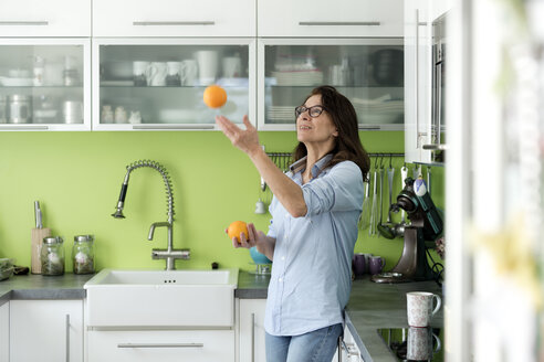 Mature woman juggling with oranges in kitchen at home - FLLF00091