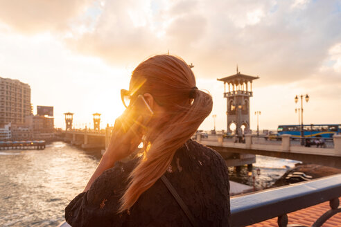 Female tourist with red hair making smartphone call near Stanley bridge at sunset, rear view, Alexandria, Egypt - CUF50150