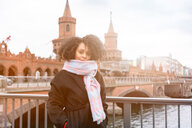 Mid adult woman in scarf on Oberbaum Bridge, portrait, Berlin, Germany - CUF50159