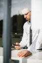 Mid adult businessman in cafe window seat looking at smartphone - CUF50177