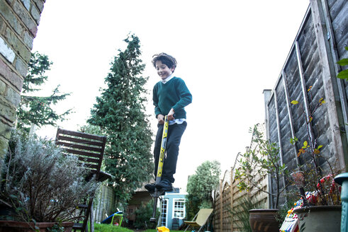 Boy jumping on pogo stick in garden - CUF50204