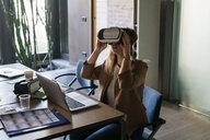 Businesswoman using virtual reality headset in office - CUF50216