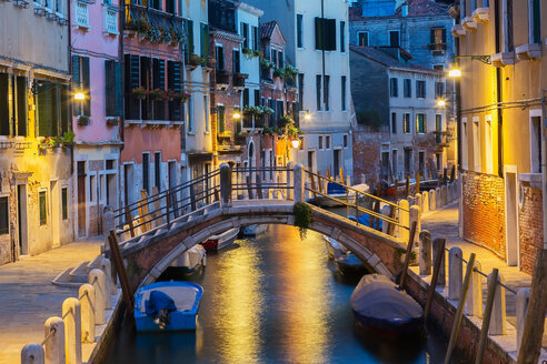 Moored boats and footbridge over Rio de la Toletta Canal, old architectural style residential buildings at dusk, Dorsoduro district, Venice, Veneto, Italy - CUF50234