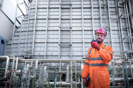 Composite image of worker using walkie talkie in powerstation - CUF50240