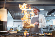 Chef cooking with brandy (flambe) and flames in Italian restaurant kitchen - CUF50258