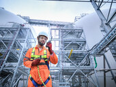 Composite image of engineer using walkie talkie in biomass plant - CUF50267