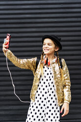 Portrait of smiling girl wearing hat and golden sequin jacket taking selfie with smartphone - ERRF00891