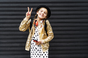 Portrait of happy girl with smartphone wearing hat and golden sequin jacket showing victory sign - ERRF00894