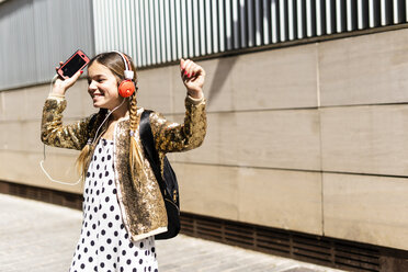 Smiling girl with headphones and smartphone dancing on the street - ERRF00900