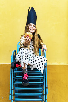 Smiling girl wearing black crown sitting on stack of chairs holding hamburger - ERRF00906