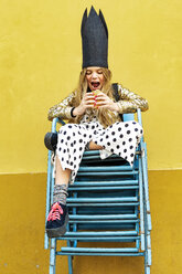 Portrait of girl wearing black crown sitting on stack of chairs eating Hamburger - ERRF00909