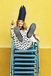 Portrait of smiling girl wearing black crown sitting on stack of chairs eating Hamburger - ERRF00912