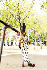Girl wearing golden sequin jacket, polka dot jumpsuit and black crown drinking soft drink on the street - ERRF00915