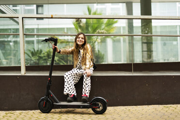 Portrait of smiling girl with E-Scooter wearing golden sequin jacket and polka dot jumpsuit - ERRF00924