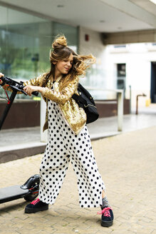 Portrait of smiling girl with E-Scooter wearing golden sequin jacket and polka dot jumpsuit tossing her hair - ERRF00927