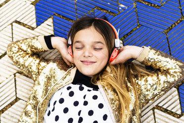Portrait of happy girl wearing golden sequin jacket listening music with headphones - ERRF00933