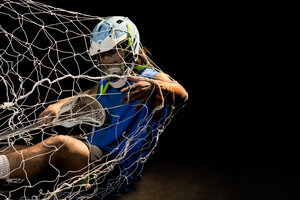 Young male lacrosse player in action falling into net, against black background - ISF21072