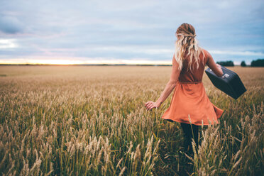 Woman swinging suitcase in wheat field, Edmonton, Canada - ISF21090