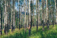 Woman doing prayer pose in forest, Banff, Canada - ISF21093