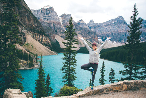 Woman practising yoga, Moraine Lake, Banff, Canada - ISF21099