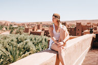 Woman enjoying view on stonewall, Ouarzazate, Souss-Massa-Draa, Morocco - ISF21105