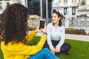 Girlfriends taking photograph in city park, Madrid, Spain - CUF50307