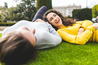 Girlfriends talking on grass in city park - CUF50310