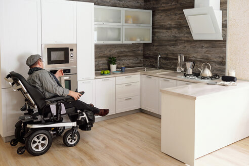 Physically impaired man switching on oven in kitchen - CUF50322