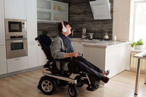 Physically impaired man listening to music with headphones at home - CUF50331