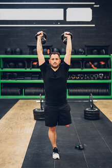 Man with disability using kettlebells in gym - CUF50334