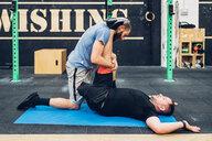 Personal trainer working with man with disability in gym - CUF50358