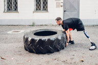 Man with prosthetic leg weight training with giant tyre - CUF50361