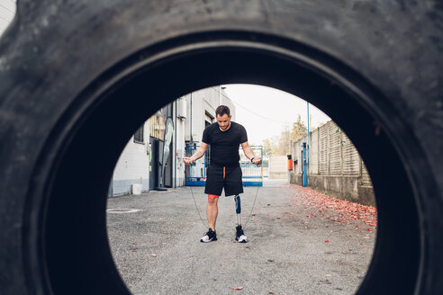 Man with prosthetic leg skipping, seen through tyre - CUF50364