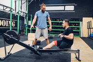 Personal trainer working with man with disability in gym - CUF50376