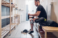 Man with prosthetic leg in gym changing room - CUF50382